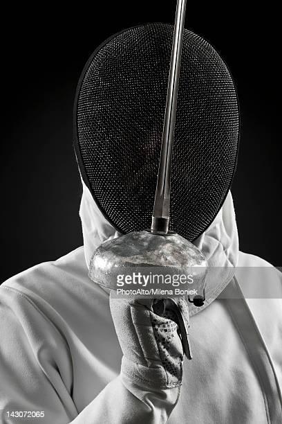Fencer holding up foil, portrait