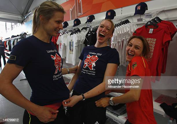 Fencers Britta Heidemann Ricarda Multerer and Monika Sozanska of Germany laugh while trying shirts in the merchandising store at the Olympic Village...