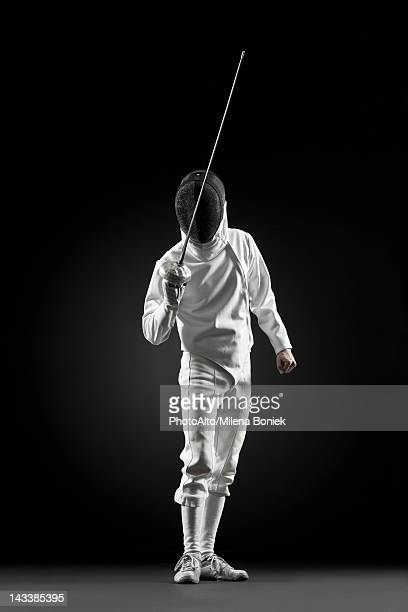 Fencers holding up foil, portrait