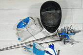 Fencing foil equipment. Three fencing foils with pistol grip (sporting weapon), a fencing mask and a blue and white glove on floor
