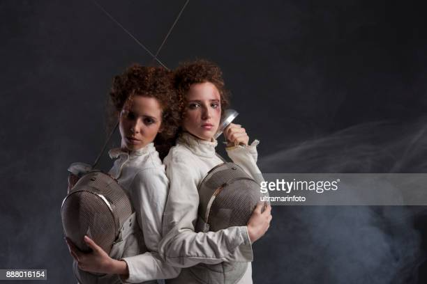 Compétition d'escrime sport. Duel. Fond gris foncé. Femmes sportives. Escrimeur de filles rousse bouclés deux lits jumeaux. Twins.
