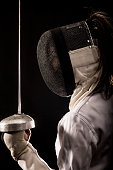 Portrait of woman wearing white fencing costume practicing with the sword. Isolated on black background.