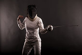 Portrait of woman wearing white fencing costume practicing with the sword.