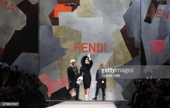 Fendi's German designers Karl Lagerfeld and Silvia Venturini Fendi acknowledge the audience next to British model Cara Delevingne at the end of...