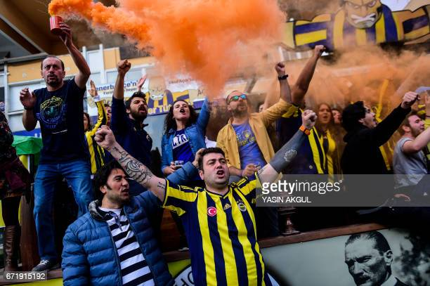 TOPSHOT Fenerbahce supporters cheers as they hold smoke flares at the TT Arena stadium before the Turkish Spor Toto Super Lig football match between...