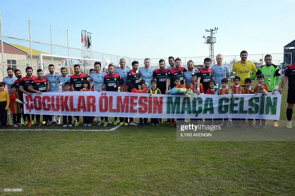 Fenerbahce's and Amedspor 'splayers stand together behind a banner which translates as ' Children shoul not die, they should come to match' before the Turkish Cup football match between Amed Spor and Fenerbahce Zirrat on February 9, 2016 in Diyarbakir. The Turkish Football Federation said on February 5, 2016 it had suspended a Kurdish player for statements considered 'ideological propaganda' on the conflict in the Kurdish-majority southeast, adding to a string of cases cracking down on freedom of expression in Turkey. AKENGIN