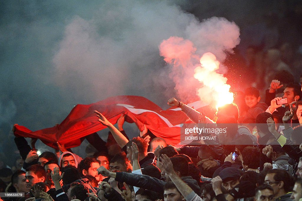 Fenerbahce's fans hold a Turkish national flag and a flare during the UEFA Europa League Group C3 football match between Olympique de Marseille and Fenerbahce SK, on November 22, 2012, at the velodrome stadium in Marseille.