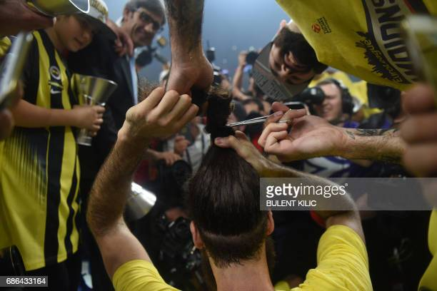 Fenerbahce's Luigi Datome gets his hair cut after winning the first place basketball match between Fenerbahce and Olympiacos at the Euroleague Final...