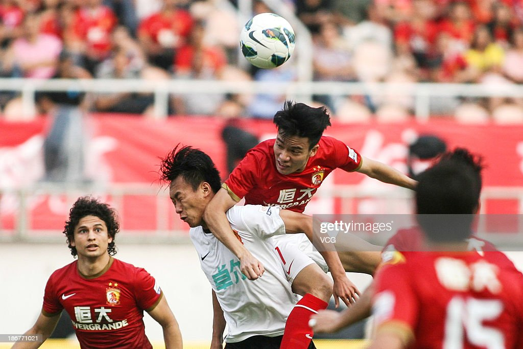 Feng Junyan #7 of Guangzhou Evergrande (3rd L) jumps to head the ball, watched by team-mate Elkeson (L) during the Chinese Super League match between Guangzhou Evergrande and Wuhan Zall at Tianhe Sports Center on November 3, 2013 in Guangzhou, China.