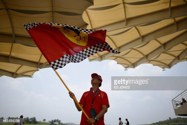 A Ferarri fan waves a flag prior to the start of the Formula One Malaysian Grand Prix at the Sepang circuit near Kuala Lumpur on March 30 2014 AFP...