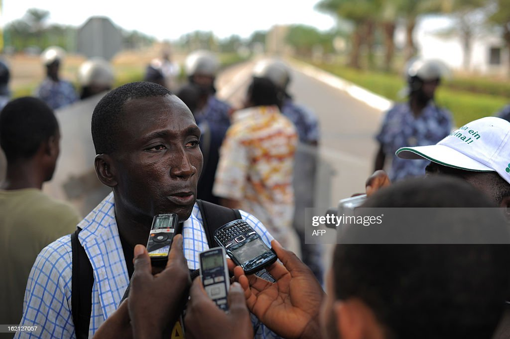 Ferdinand Ayite, president of the SOS -Journalist in Danger speaks to the press as behind security forces stand to prevent a crowd of several hundred journalists and members of the public from protesting in front of the Palais des Congres in Lome on February 19, 2013. Journalists in Togo are protesting against a law giving the High Authority of Audiovisual and Communication (HAAC) more power to control media in Togo.