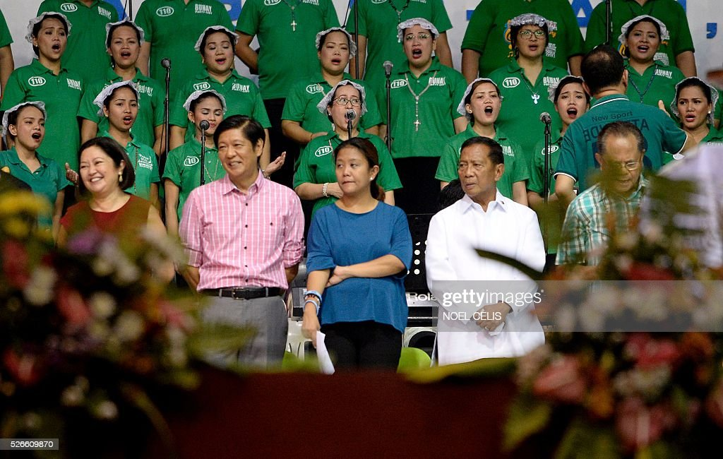Ferdinand Marcos Jr., son of the late Philippine dictator Ferdinand Marcos and a vice-presidential candidate for the May 9 elections (2nd L) and Philippine Presidential candidate and Vice President Jejomar Binay (2nd R), Head of El Shaddai Mike Velarde (R) at the the Pro-Catholic Born again religious group El Shaddai prayer vigil overnight celebration in Manila on May 1, 2016. More than 17,000 positions ranging from president to town councillors will be contested when the Philippines holds national elections on May 9, 2016. About 80 percent of the Philippines' 100 million people are Catholic, a legacy of Spanish colonial rule that ended in the late 1800s. / AFP / NOEL