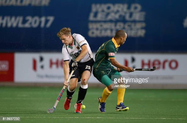 Ferdinand Weinke of Germany and Ignatius Malgraff of South Africa battle for possession during day 3 of the FIH Hockey World League Semi Finals Pool...