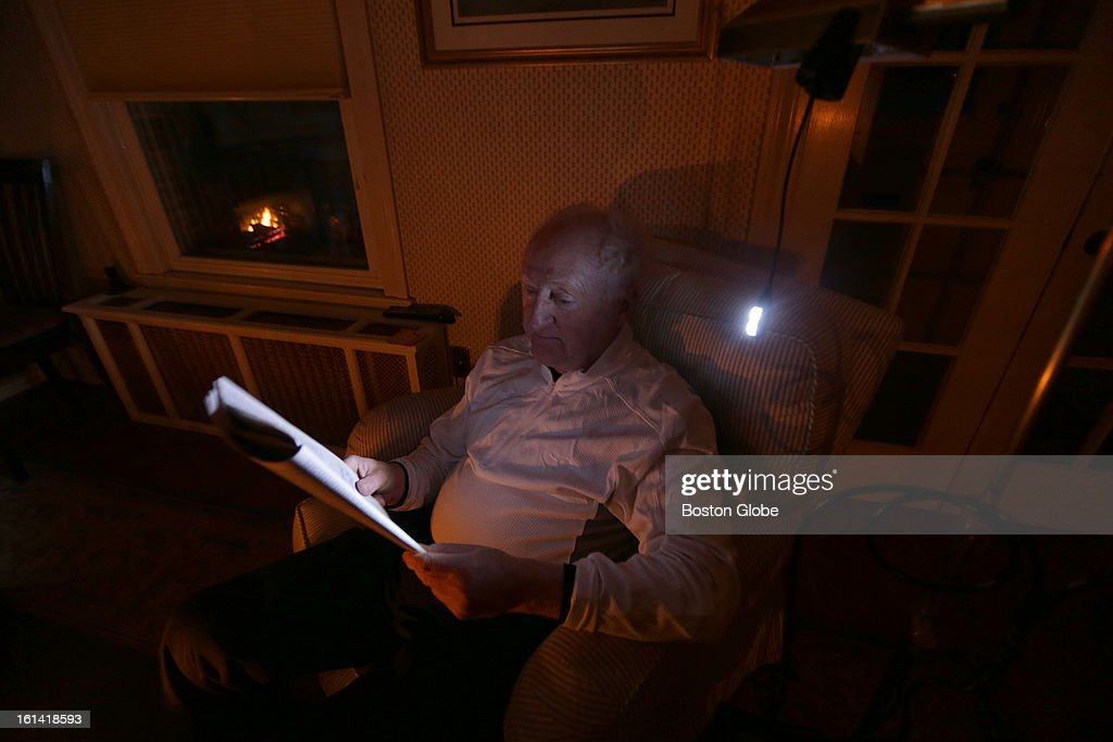 Fergus Moylan, 68, of Plymouth, reads by the light of his battery-fed reading light as he prepares to weather another night without power on Sunday, Feb. 10, 2013, after a blizzard hit New England.