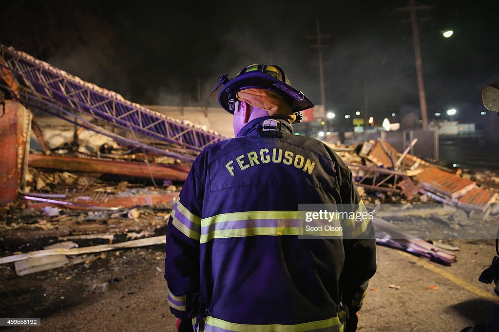 A Ferguson firefighter surveys rubble at a strip mall that was set on fire when rioting erupted following the grand jury announcement in the Michael Brown case on November 25, 2014 in Ferguson, Missouri. Brown, an 18-year-old black man, was killed by Darren Wilson, a white Ferguson police officer, on August 9. At least 12 buildings were torched and more than 50 people were arrested during the night-long rioting.