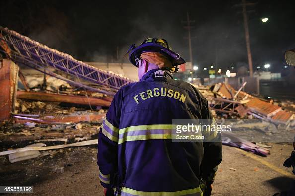 Ferguson firefighter surveys rubble at a strip mall that was set on fire when rioting erupted following the grand jury announcement in the Michael...