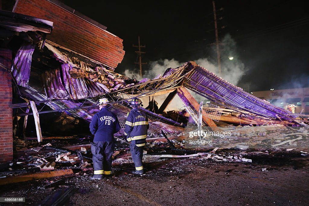 Ferguson firefighters survey rubble at a strip mall that was set on fire when rioting erupted following the grand jury announcement in the Michael Brown case on November 25, 2014 in Ferguson, Missouri. Brown, an 18-year-old black man, was killed by Darren Wilson, a white Ferguson police officer, on August 9. At least 12 buildings were torched and more than 50 people were arrested during the night-long rioting.