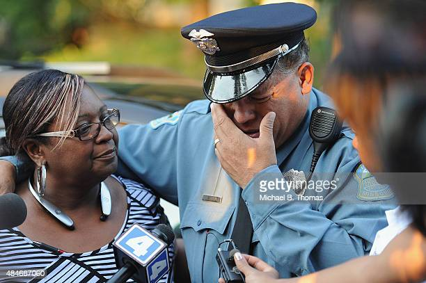 Ferguson Police officer Greg Casem is overcome with emotion during a candlelight vigil held in honor of Jamyla Bolden on August 20 2015 in Ferguson...