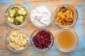 a set of fermented food great for gut health - top view of glass bowls against grunge wood:  cucumber pickles,  coconut milk yogurt, kimchi, sauerkraut, red beets, apple cider vinegar