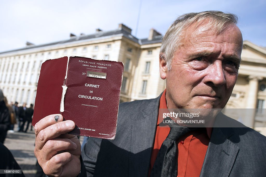 Fernand Delage, member of the Roma community, shows a travel permit delivered by French authorities as he takes part in the 2nd edition of the Roma Pride, a Europe wide event aiming at fighting racism towards Roma people, protecting their equal rights and celebrating their identity on October 7, 2012 near the Pantheon in Paris.