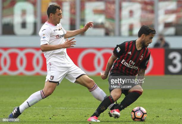 Fernandez Suso of AC Milan is challenged by Mato Jajalo of US Citta di Palermo during the Serie A match between AC Milan and US Citta di Palermo at...
