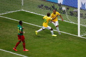 Fernandinho of Brazil celebrates scoring his team's fourth goal with Ramires as Henri Bedimo of Cameroon looks on during the 2014 FIFA World Cup...