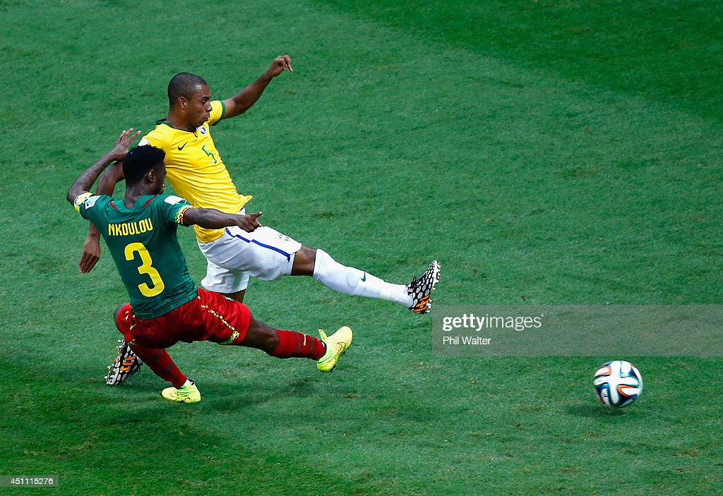 Fernandinho of Brazil scores his team's fourth goal against Nicolas N'Koulou of Cameroon during the 2014 FIFA World Cup Brazil Group A match between Cameroon and Brazil at Estadio Nacional on June 23, 2014 in Brasilia, Brazil.