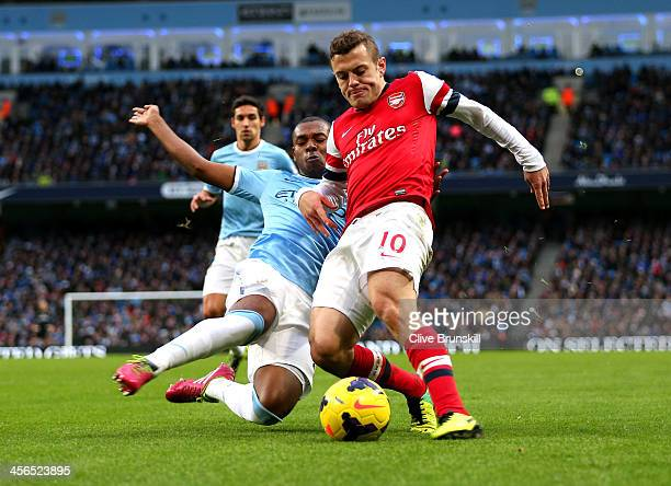 Fernandinho of Manchester City and Jack Wilshere of Arsenal battle for the ball during the Barclays Premier League match between Manchester City and...