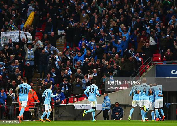 Fernandinho of Manchester City celebrates with team mates and fans as he scores their first goal during the Capital One Cup Final match between...