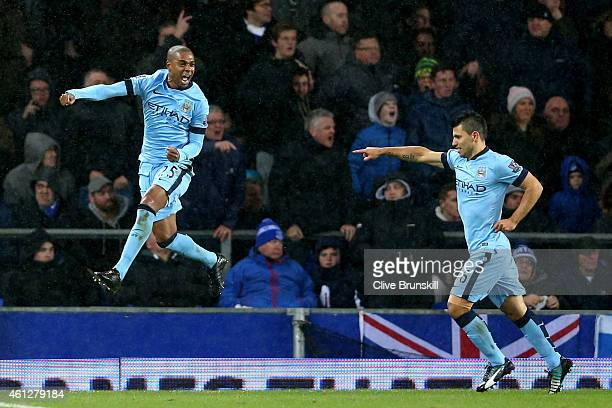 Fernandinho of Manchester City celebrates with teammate Sergio Aguero after scoring the opening goal during the Barclays Premier League match between...