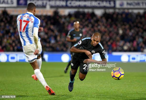 Fernandinho of Manchester City dives past Rajiv van La Parra of Huddersfield Town which led to a yellow card during the Premier League match between...