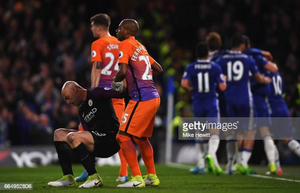 Fernandinho of Manchester City helps up his team mate Willy Caballero of Manchester City during the Premier League match between Chelsea and...