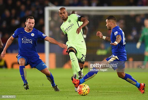 Fernandinho of Manchester City is challenged by Danny Drinkwater and Danny Simpson of Leicester City during the Barclays Premier League match between...