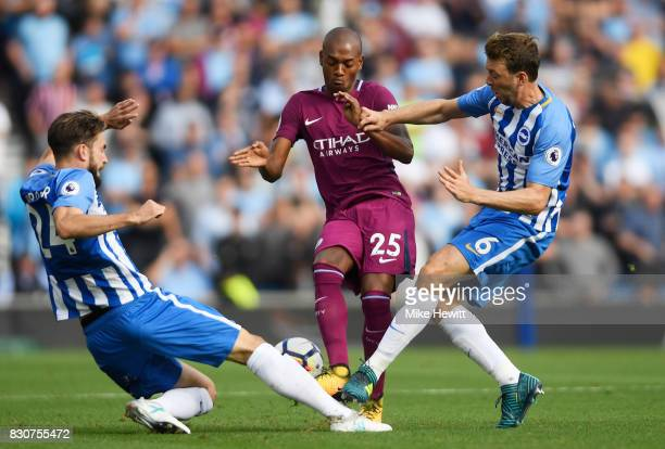 Fernandinho of Manchester City is tackled by Masato Morishige of Brighton and Hove Albion and Dale Stephens of Brighton and Hove Albion during the...