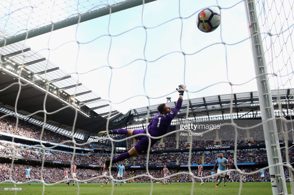 Fernandinho of Manchester City (obscure) scores his sides fifth goal as Jack Butland of Stoke City attempts to stop it during the Premier League match between Manchester City and Stoke City at Etihad Stadium on October 14, 2017 in Manchester, England.