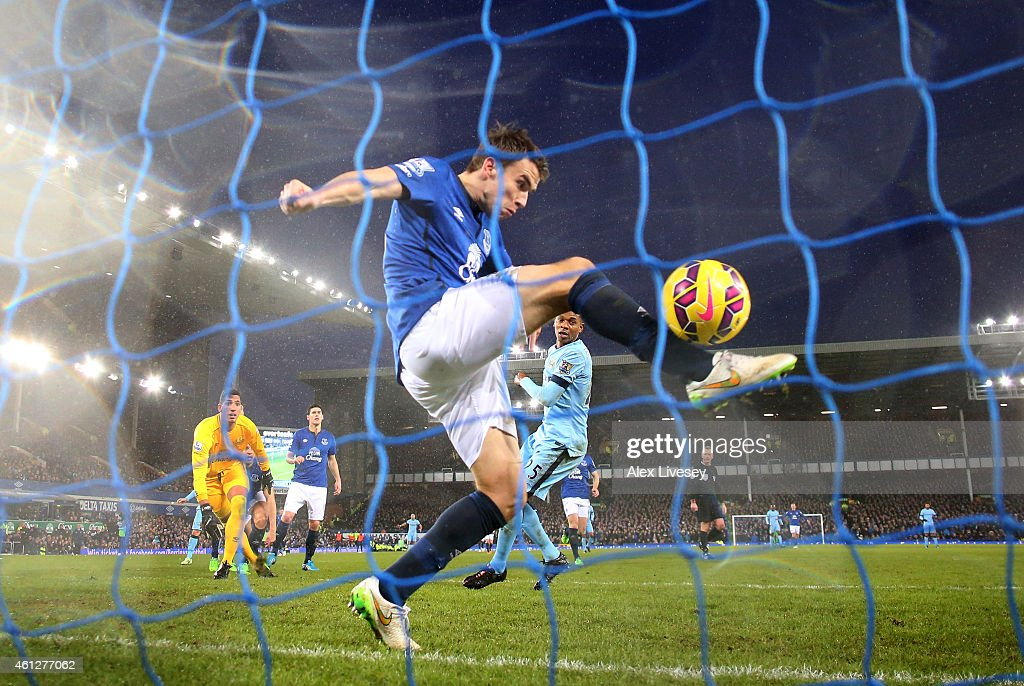 Fernandinho of Manchester City scores the opening goal despite the goal line efforts from Seamus Coleman of Everton during the Barclays Premier League match between Everton and Manchester City at Goodison Park on January 10, 2015 in Liverpool, England.