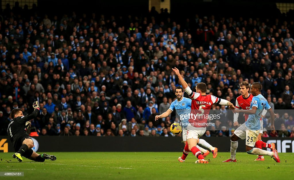 <a gi-track='captionPersonalityLinkClicked' href=/galleries/search?phrase=Fernandinho+-+Soccer+Player+-+Manchester+City&family=editorial&specificpeople=10093285 ng-click='$event.stopPropagation()'>Fernandinho</a> of Manchester City scores their fifth goal past <a gi-track='captionPersonalityLinkClicked' href=/galleries/search?phrase=Wojciech+Szczesny&family=editorial&specificpeople=6539507 ng-click='$event.stopPropagation()'>Wojciech Szczesny</a> of Arsenal during the Barclays Premier League match between Manchester City and Arsenal at Etihad Stadium on December 14, 2013 in Manchester, England.