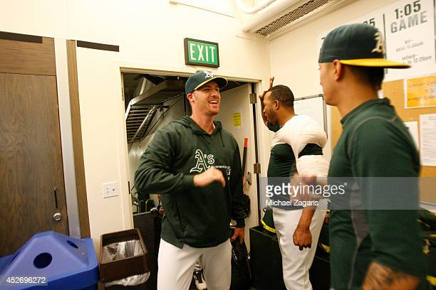 Fernando Abad and Jesse Chavez of the Oakland Athletics congratulate Eric O'Flaherty in the clubhouse following the game against the San Francisco...