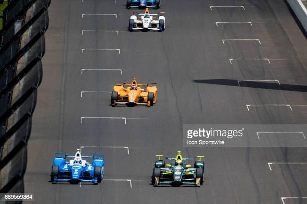Fernando Alonso driver of the McLarenHondaAndretti Honda chases down Scott Dixon driver of the Chip Ganassi Racing Honda and Ed Carpenter driver of...