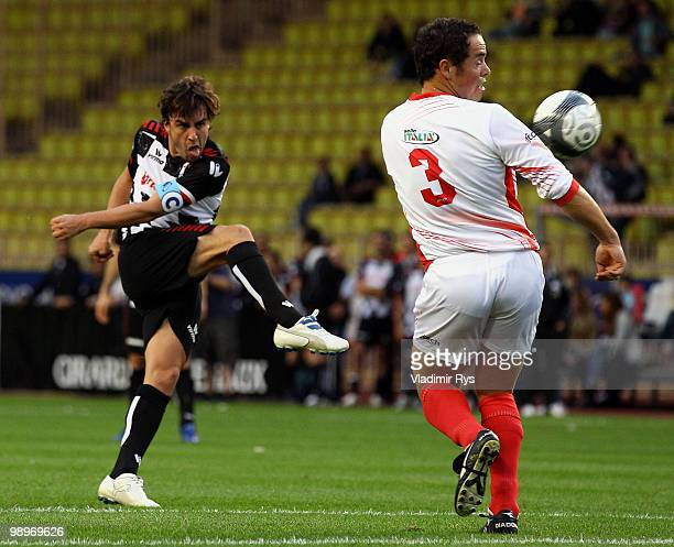 Fernando Alonso of Ferrari and Spain shoots his team's first goal as Peter Fill defends during the football charity match between the Monaco star...