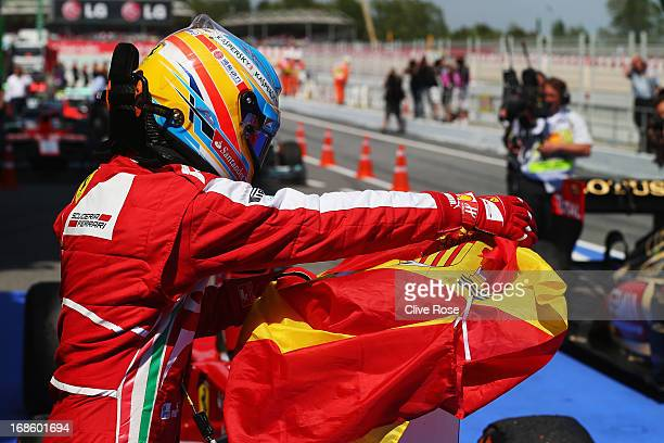 Fernando Alonso of Spain and Ferrari celebrates by putting his national flag on the number one sign in parc ferme after winning the Spanish Formula...