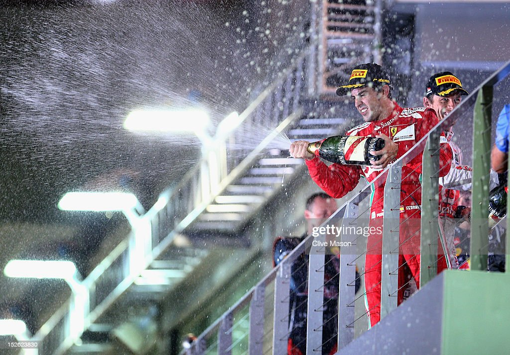Fernando Alonso of Spain and Ferrari celebrates on the podium after finishing third during the Singapore Formula One Grand Prix at the Marina Bay Street Circuit on September 23, 2012 in Singapore, Singapore.