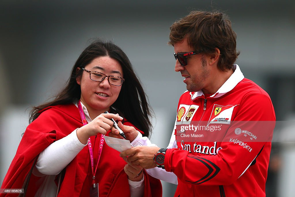 Fernando Alonso of Spain and Ferrari signs an autograph for a fan as he walks through the paddock ahead of the Chinese Formula One Grand Prix at the Shanghai International Circuit on April 17, 2014 in Shanghai, China.