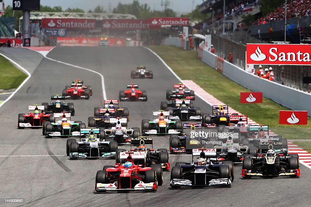 Fernando Alonso of Spain and Ferrari takes the lead from Pastor Maldonado of Venezuela and Williams into the first corner at the start of the Spanish...