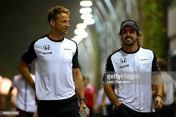 Fernando Alonso of Spain and McLaren Honda and Jenson Button of Great Britain and McLaren Honda walk in the paddock during practice for the Formula...