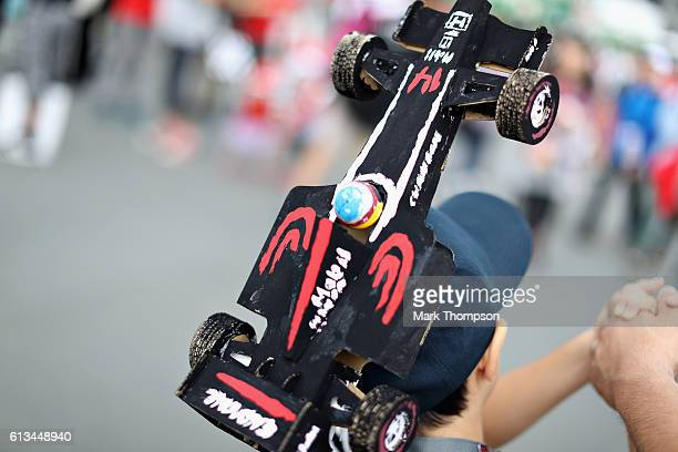 Fernando Alonso of Spain and McLaren Honda fan with a car model hat in the fan zone before the Formula One Grand Prix of Japan at Suzuka Circuit on...
