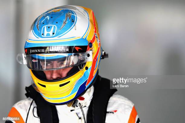 Fernando Alonso of Spain and McLaren Honda looks on in the garage during practice for the Malaysia Formula One Grand Prix at Sepang Circuit on...