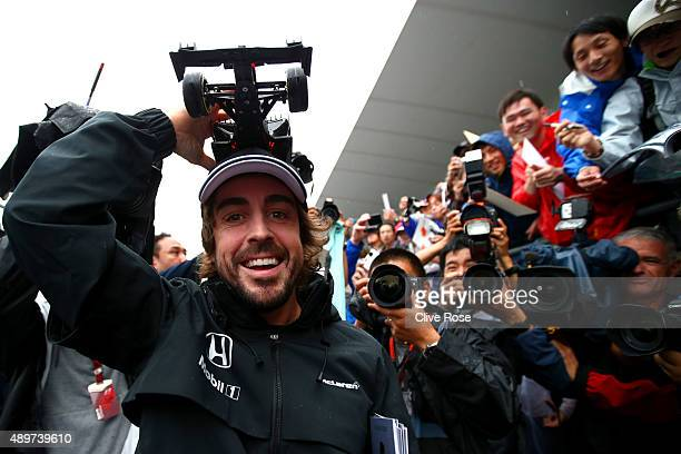 Fernando Alonso of Spain and McLaren Honda poses with a fan's cap before signing it during previews to the Formula One Grand Prix of Japan at Suzuka...