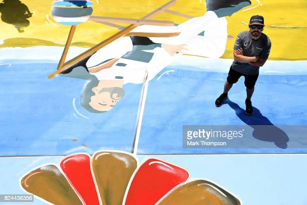 Fernando Alonso of Spain and McLaren Honda poses with a painting of himself on a deck chair in the Paddock before the Formula One Grand Prix of...