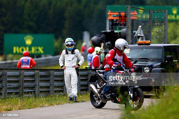 Fernando Alonso of Spain and McLaren Honda waits for a lift back to the paddock after crashing during the Formula One Grand Prix of Austria at Red...